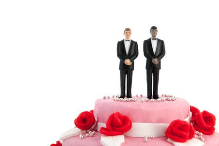 Foto de Pink wedding cake with red roses and gay couple on top - Imagen libre de derechos