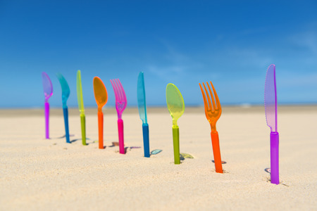 Photo pour Colorful silverware standing in sand at the beach - image libre de droit