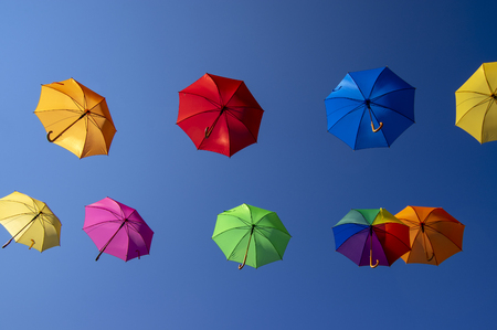 Foto de Group of flying umbrellas isolated on blue background, ready for the rain, wallpaper background, bright various colors, beautiful still life - Imagen libre de derechos