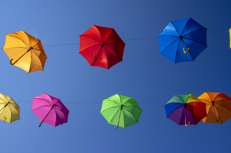 Foto de Group of flying umbrellas isolated on blue background, ready for the rain, wallpaper background, bright various colors, beautiful scene - Imagen libre de derechos