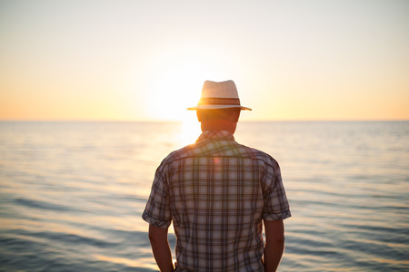 Photo pour man standing backlight sunset lighting back view summer evening beach - image libre de droit