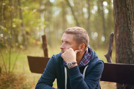 Foto de man thinking moody portrait, sitting at autumn park, selective focus - Imagen libre de derechos