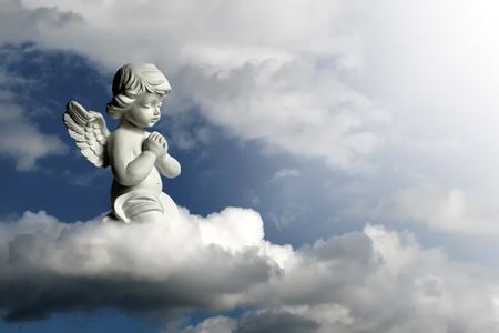 Photo pour Guardian angel kneeling and praying. Angel guardian on the cloud - image libre de droit