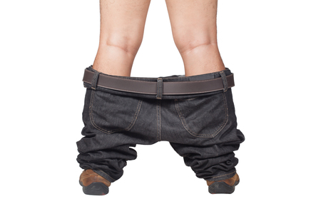 Foto de Caught with your pants down - man in brown shoes and jeans dropped down standing on floor, isolate on white background - Imagen libre de derechos