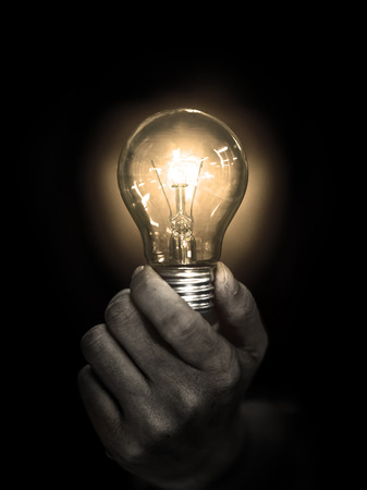 Foto de lightbulb hold in hand on black background - Imagen libre de derechos