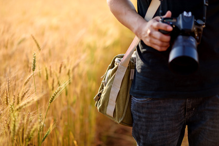 Photo for Photographer holding camera on wheat fields in warm sunset - Royalty Free Image