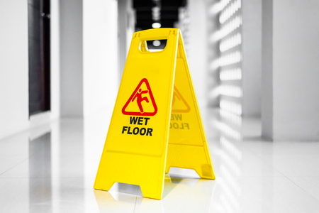 Photo for Sign showing warning of wet floor on wet floor in sunrise - Royalty Free Image