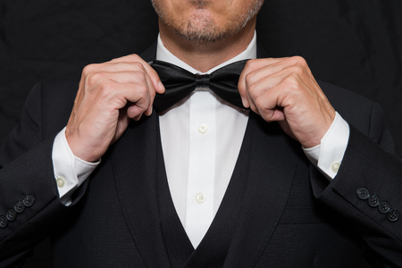 Photo for Close-up of a gentleman wearing Black Tie straightens his bowtie. - Royalty Free Image
