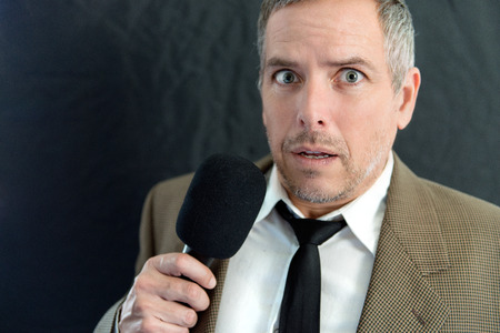 Photo for Close-up of an anxious man speaking into microphone. - Royalty Free Image