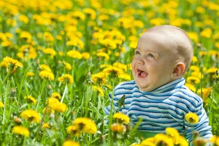 happy baby sitting in flowers meadow