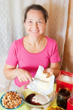 Mature woman adds margarine into dish. One of the stages of cooking of honey cake. See series