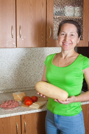 Woman with food products for stuffed vegetable marrow. See in series stages of cooking of stuffed vegetable marrow