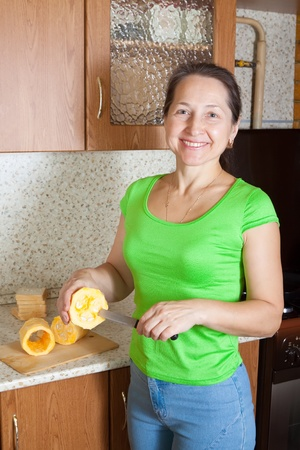 Woman cooking stuffed vegetable marrow in her kitchen. See in series stages of cooking of stuffed vegetable marrow.
