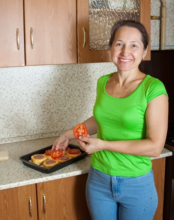 Woman adds tomato on stuffed vegetable marrow. See in series stages of cooking of stuffed vegetable marrow