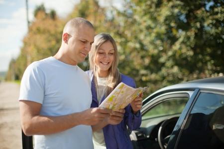 Photo pour tourist couple looking at the map on the road. Focus on woman - image libre de droit