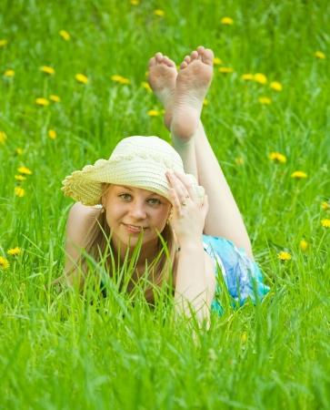 girl in hat lying in meadow grass