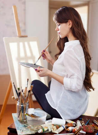 Photo for female artist with oil colors and brushes near  easel with blank canvas - Royalty Free Image
