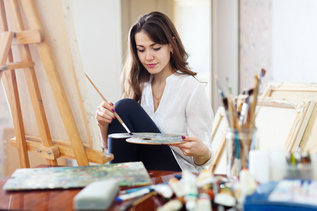 Photo for Long-haired beautiful artist paints on canvas in workshop - Royalty Free Image