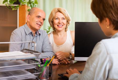 Foto de Positive senior couple opening saving account in bank - Imagen libre de derechos