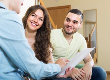 Foto de Positive young couple discussing details of private insurance with agent - Imagen libre de derechos