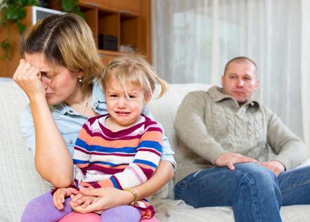 Photo pour Family conflict. Dismal woman with children against husband after quarrel at home - image libre de droit