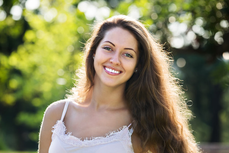 Outdoor portrait of smiling long-haired woman