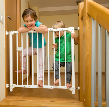 Photo pour Two baby girls approaching safety gate of  stairs - image libre de droit