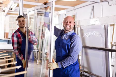 Photo pour Two production workers  inspecting windows at workshop - image libre de droit