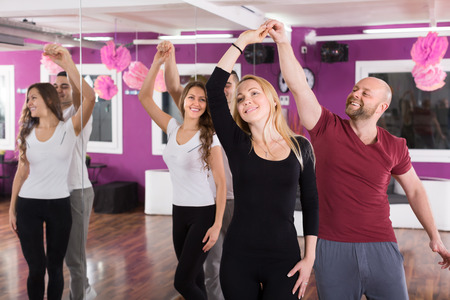 Group of joyful smiling young adults dancing salsa at dance class