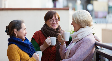 Photo for Mature women in warm clothes having cup of hot tea on terrace - Royalty Free Image