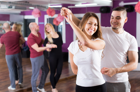 Foto de Two young smiling couples having dancing class in club - Imagen libre de derechos