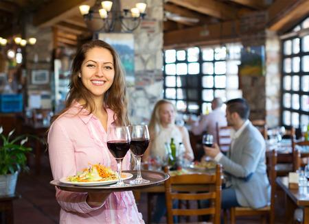 Photo pour Portrait of smiling  adults having dinner and respectful waiter - image libre de droit