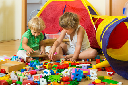 Photo pour Calm children playing with toys in home interior - image libre de droit