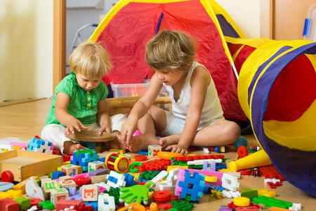 Foto de Calm children playing with toys in home interior - Imagen libre de derechos
