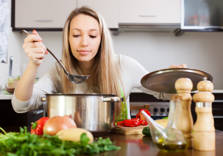 Ordinary woman  with ladle cooking soup in domestic kitchen