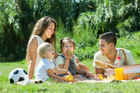 Foto de Young cheerful family with little daughters having holiday with picnic at park in summer day - Imagen libre de derechos