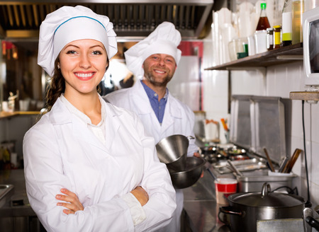 Foto de Happy  chef and cook  working  in restaurant kitchen - Imagen libre de derechos