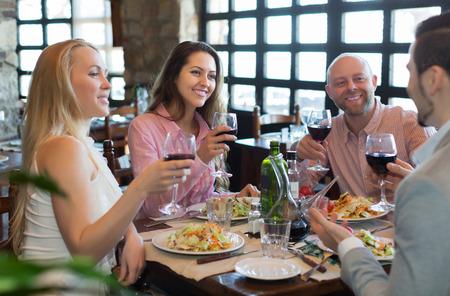 Photo pour Portrait of smiling young adults having dinner in family restaurant. Focus on brunette girl - image libre de droit