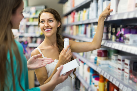 Photo pour Happy russian girl buying cosmetical cream in the shopping mall - image libre de droit