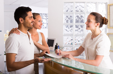 Photo for Positive young couple talking with secretary at reception in the clinic - Royalty Free Image
