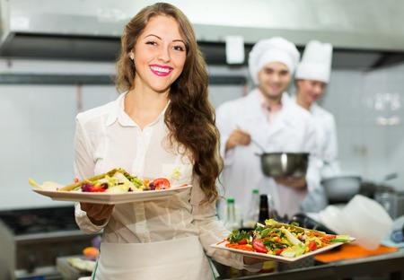 Photo pour Team of chefs and young beautiful waiter at restaurant kitchen - image libre de droit