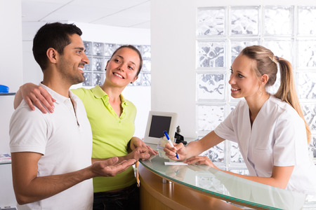 Photo pour Positive young couple talking with smiling secretary at reception in the clinic - image libre de droit