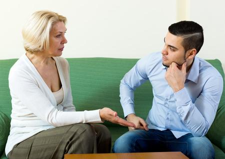 Foto de Attractive man and his mature girlfriend having serious conversation indoors - Imagen libre de derechos