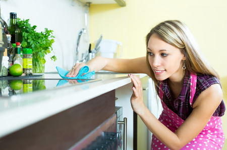 Photo pour Attractive woman cleaning furniture in kitchen with a rag - image libre de droit