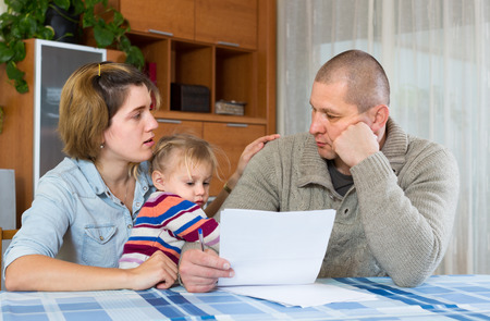 Foto de Worried family with child sitting with financial documents at home - Imagen libre de derechos