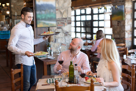 Photo pour Couple eating delicious and fresh salads in a restaurant while waiter brings them more vegetarian food - image libre de droit