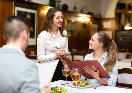Photo pour Hospitable waitress taking an order from a couple in a rural restaurant - image libre de droit