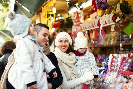 Foto de Happy family choosing Christmas decoration at Christmas market. Focus on woman and her daughter - Imagen libre de derechos