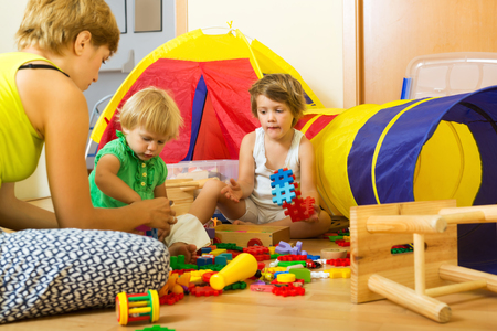Photo pour Young mother and children playing with  toys in home - image libre de droit