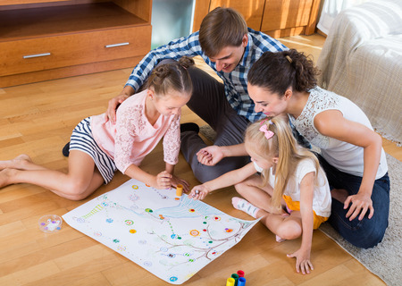 Foto de Young smiling parents and two little daughters playing board game at home - Imagen libre de derechos